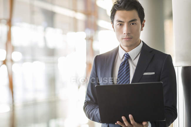 Chinese businessman standing with laptop indoors — Stock Photo