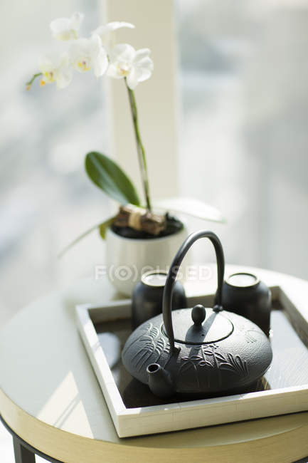 Tasses de thé et théière sur table avec plante orchidée — Photo de stock