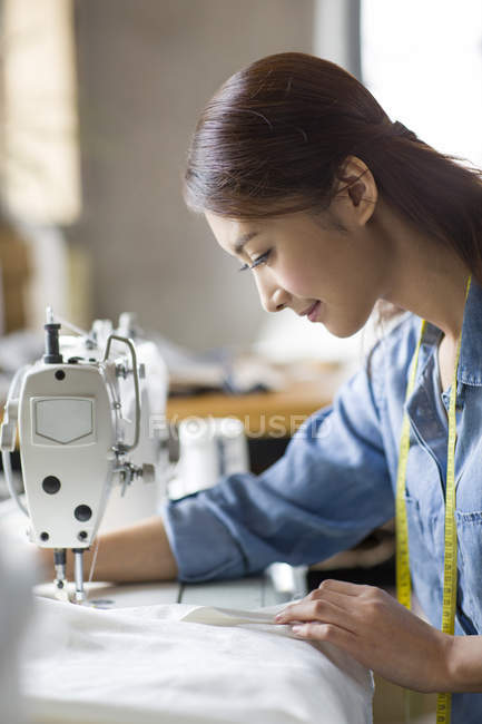 Chinese female tailor using sewing machine, side view — Stock Photo