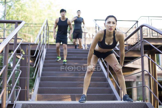 Mulher chinesa descansando após correr atrás de escadas — Fotografia de Stock
