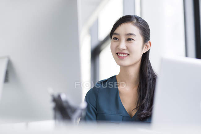 Chinese businesswoman sitting at workplace in office — Stock Photo