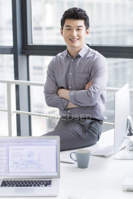 Chinese businessman sitting on office table with arms folded — Stock Photo