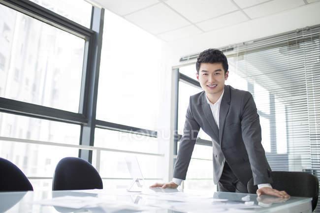 Empresario chino apoyado en la mesa en la oficina - foto de stock