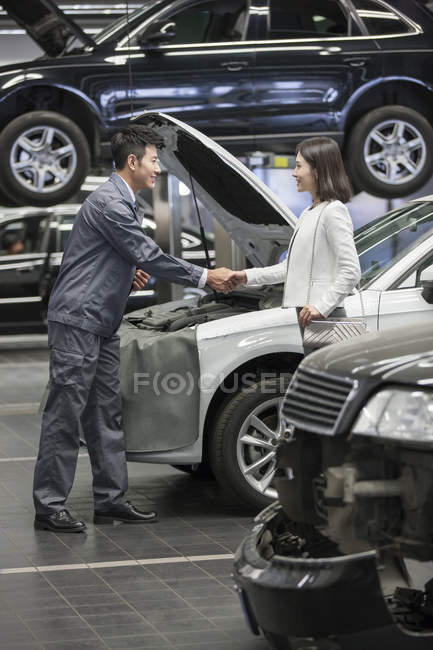 Chinese auto mechanic and car owner shaking hands — Stock Photo
