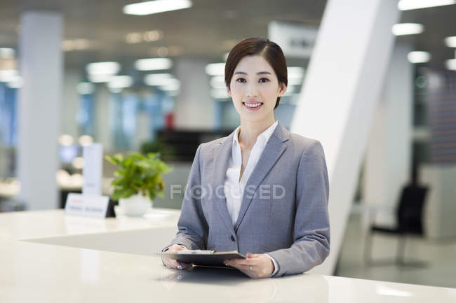 Chinese receptionist at reception counter — Stock Photo