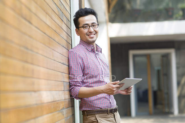 Homem chinês apoiando-se na parede de tijolo e segurando tablet digital — Fotografia de Stock