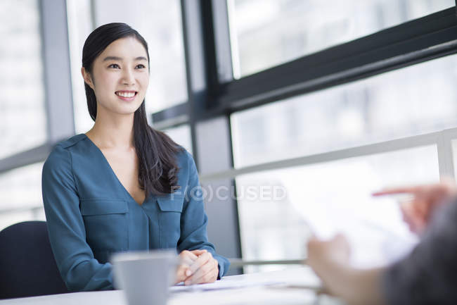 Китайская женщина, сидящая на встрече в офисе — стоковое фото