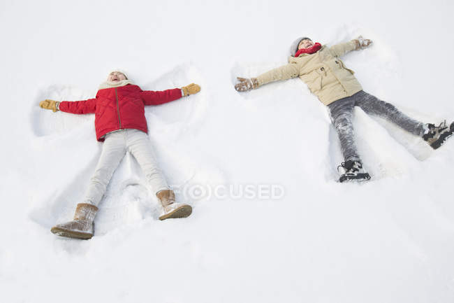 Happy children making snow angels — Stock Photo
