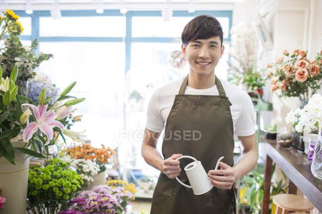 Китайский флорист, стоящий в цветочном магазине с лейкой — стоковое фото