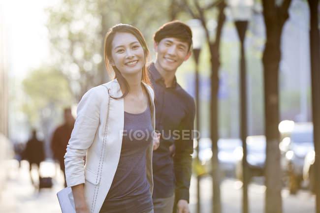 Cinese coppia che si tiene per mano mentre cammina sul marciapiede — Foto stock