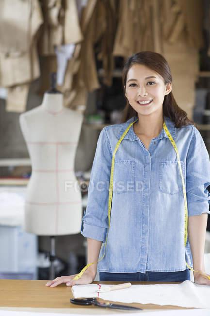 Retrato de diseñadora de moda china en la mesa en el taller - foto de stock