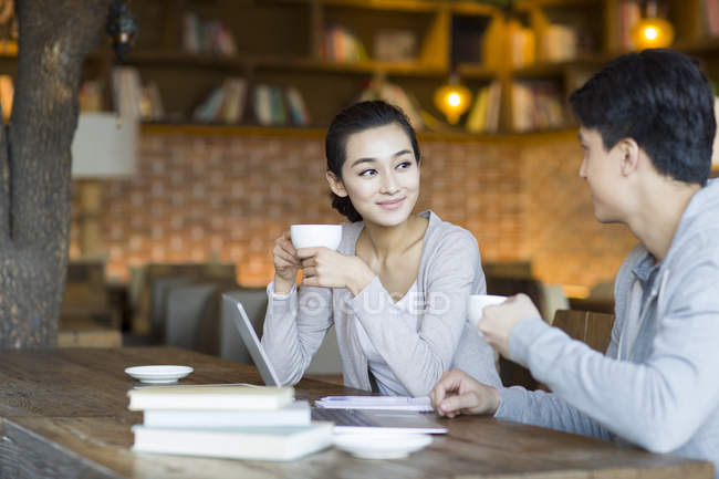 Chinese students talking in cafe with coffee — Stock Photo