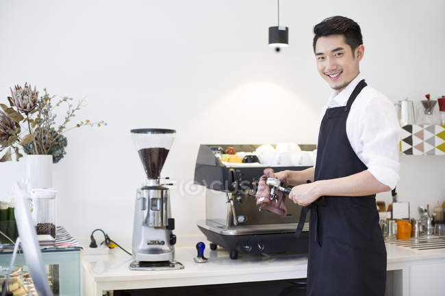 Chinese barista wiping appliance in coffee shop — Stock Photo