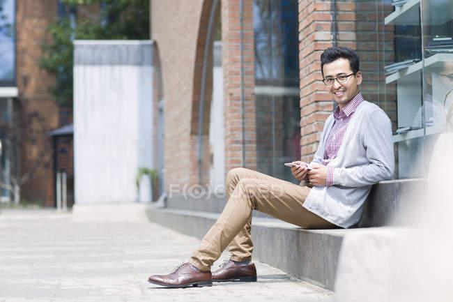 Uomo cinese seduto sulla strada e in possesso di smartphone — Foto stock