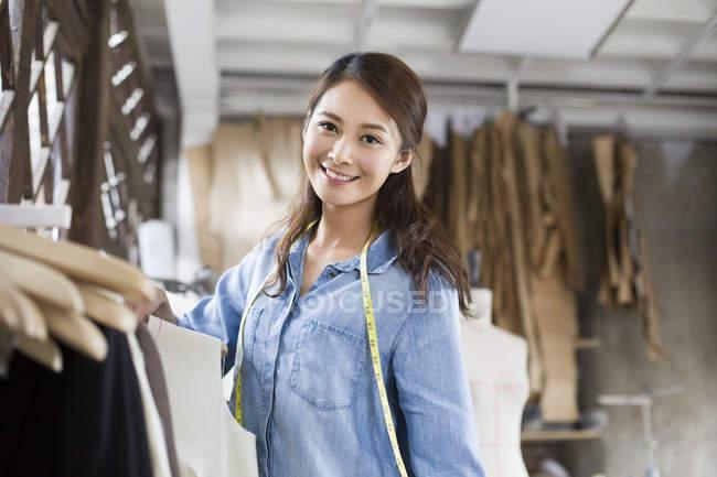 Créatrice de mode chinoise debout au porte-vêtements dans la boutique — Photo de stock