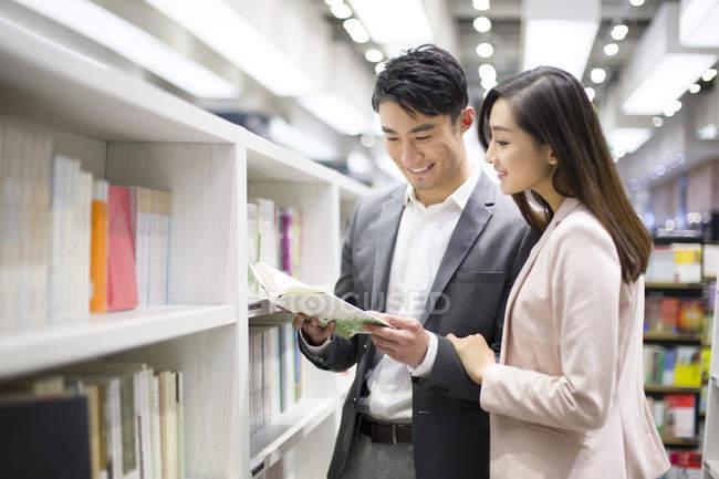 Chinesisches paar Lesebuch in Buchhandlung — Stockfoto