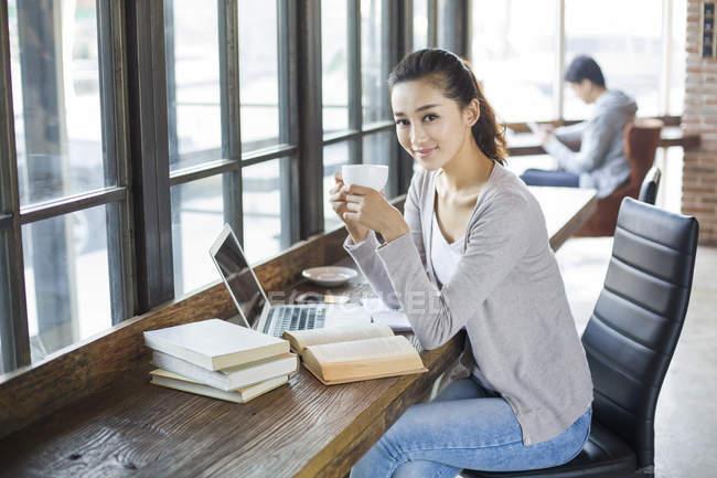 Estudante chinesa sentada no café com café — Fotografia de Stock