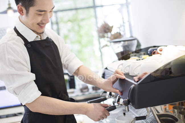 Chinese barista making coffee in cafe — Stock Photo