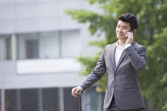 Китайский бизнесмен разговаривает по телефону с чемоданом — стоковое фото