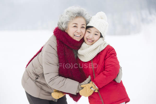 Chinese grandmother and granddaughter embracing on snow — Stock Photo