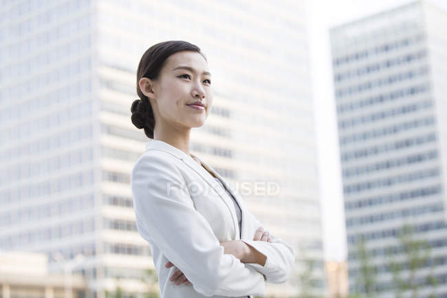 Chinese businesswoman looking at view in financial district — Stock Photo
