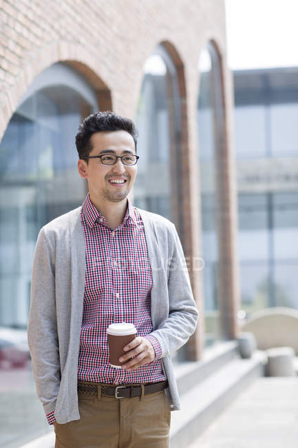 Chinese man holding cup of coffee — Stock Photo