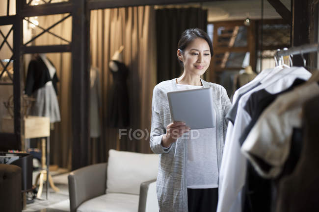 Chinese clothing store owner standing with digital tablet — Stock Photo