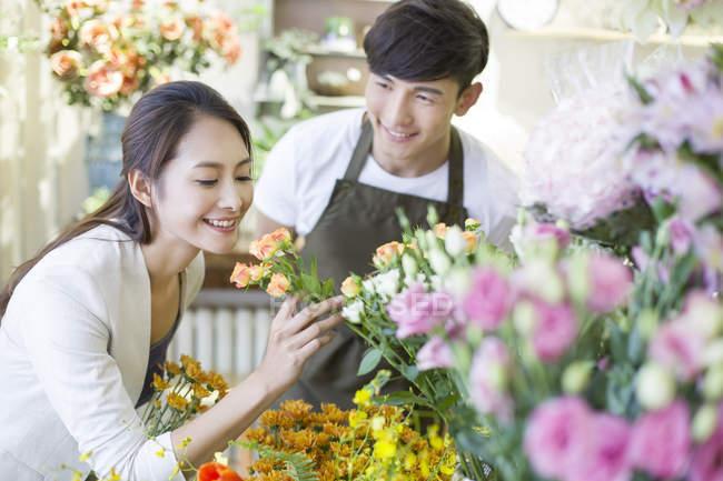 Китаянка, нюхающая розы в магазине с флористом — стоковое фото