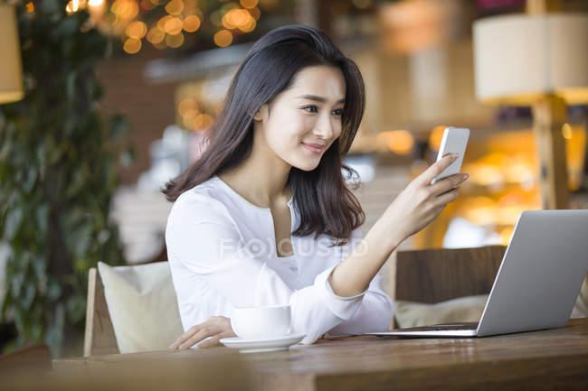 Donna cinese utilizzando smartphone nella caffetteria — Foto stock