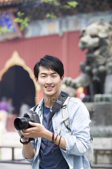 Chinese man visiting Lama Temple with digital camera — Stock Photo