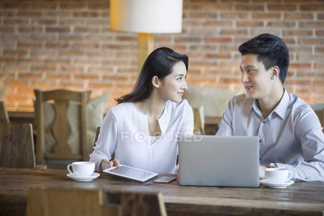 Chinese man and woman talking with laptop in cafe — Stock Photo