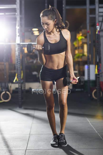 Chinese woman lifting dumbbells at gym — Stock Photo