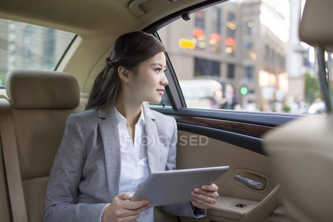 Chinesische Geschäftsfrau nutzt digitales Tablet im Auto — Stockfoto
