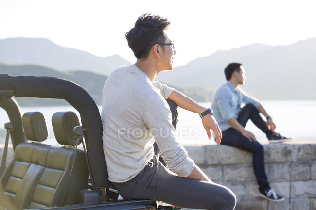 Chinese men sitting on lakeside and looking away — Stock Photo