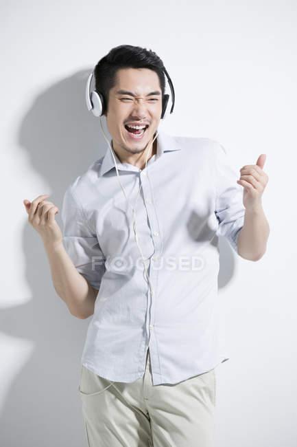 Felice giovane cinese ascoltando musica — Foto stock