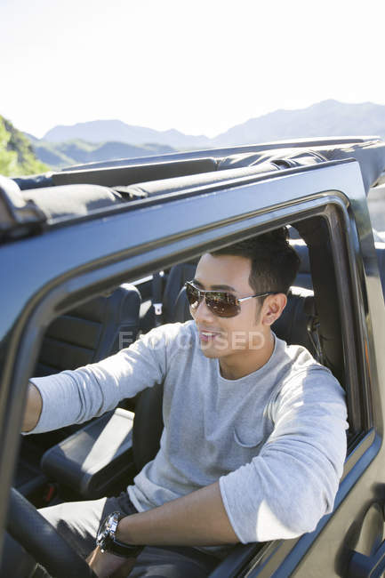 Chinese man driving car and smiling — Stock Photo