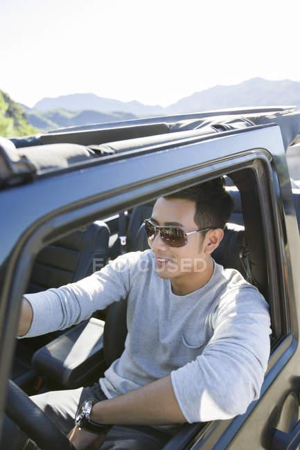 Homme chinois au volant de voiture et souriant — Photo de stock
