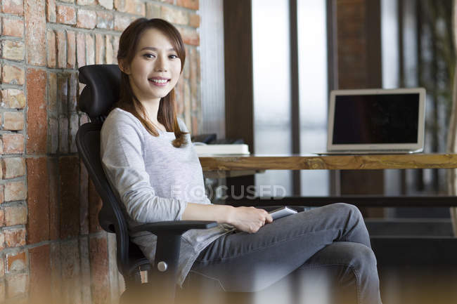 Chinese woman sitting in chair at desk in office — Stock Photo