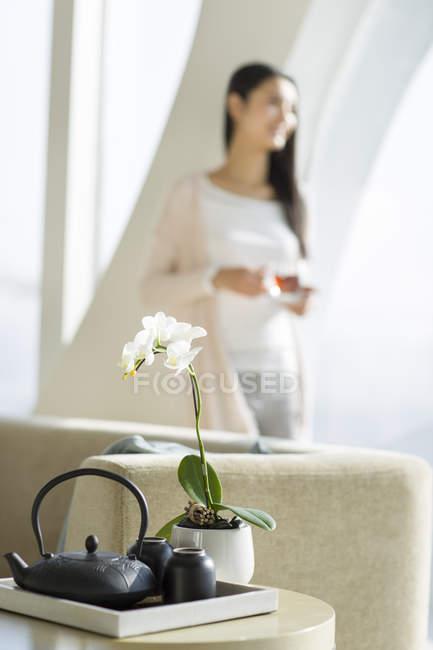 Gros plan de tasses de thé et théière sur table avec femme boire du thé noir en arrière-plan — Photo de stock