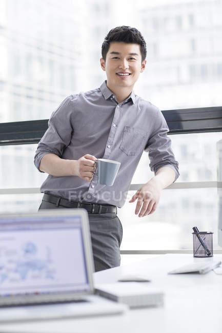 Chinesischer Unternehmer halten Tasse Kaffee im Büro — Stockfoto