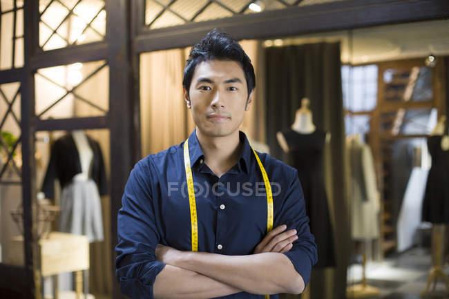Créateur de mode chinois homme debout avec les bras pliés dans la boutique — Photo de stock