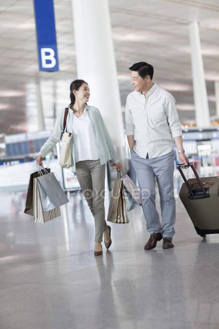 Зрелые, Китайская пара прогулки в аэропорту с сумки — стоковое фото