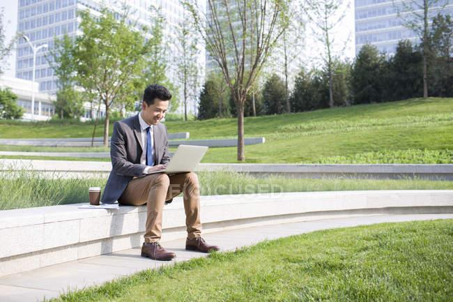 Китайский бизнесмен использует ноутбук в зеленой зоне — стоковое фото