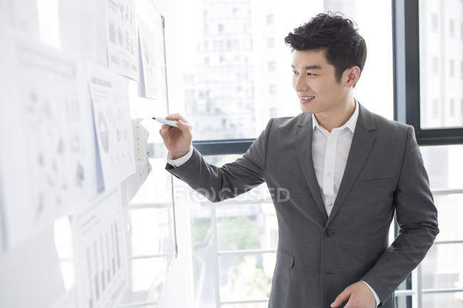 Chinese businessman writing on whiteboard in office — Stock Photo