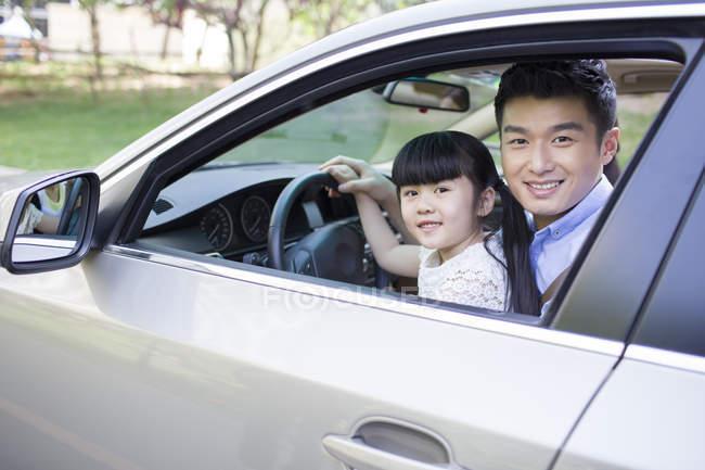 Père de chinois assis avec sa fille dans la voiture — Photo de stock