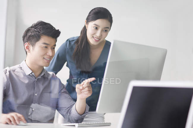 Chinese co-workers using computer in office — Stock Photo