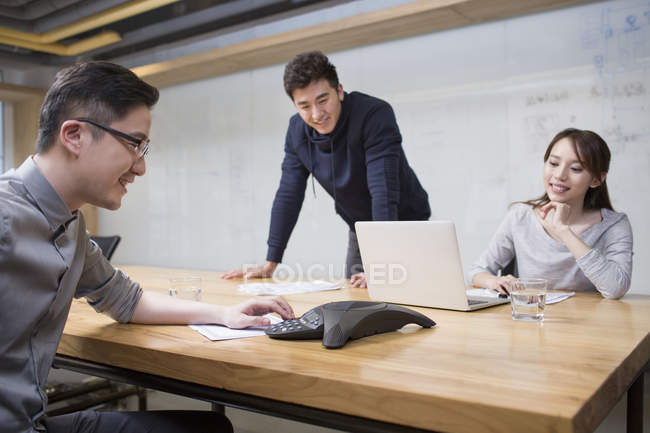 Chinese co-workers having teleconference in meeting room — Stock Photo