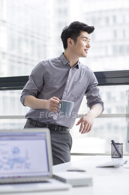 Chinese businessman standing with coffee in office — Stock Photo