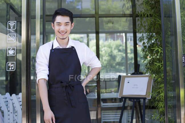 Shopkeeper standing in doorway of coffee shop — Stock Photo