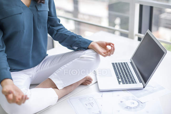 Woman meditating on office table — Stock Photo